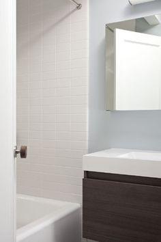 Hallway bathroom midcentury bathroom.  White subway tile in line (not running bond) very clean and modern looking.