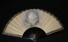 a 19th century fan. The leaf is painted with cherubs by E. Albert and it has a black lace surround, the lace measures 7cms in height from the main leaf. The sticks are tortoiseshell with initials on the guard stick.