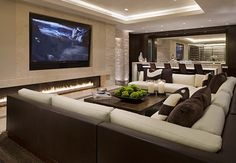10 Media Rooms We'd Love to Watch the Super Bowl In  There's a lot to be said for this subterranean salon. The larger-than-life screen makes it the ideal spot for watching the big game, but the upscale design is just as eye-catching. With a striking glass enclosed fireplace, two-tone couch, marble detailing and adjacent bar, this media room is the ultimate space for entertaining even when the game isn't on.