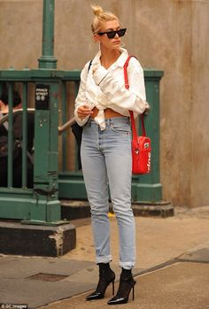Hailey Baldwin shows hint of midriff in tied up white shirt and jeans #dailymail