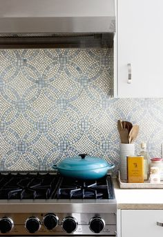 Exquisite kitchen features white lacquer cabinets paired with tan countertops and Ann Sacks mosaic tile backsplash in blue and gray.