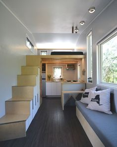Living room, staircase, lofted bedroom, and open kitchen in a tiny house.