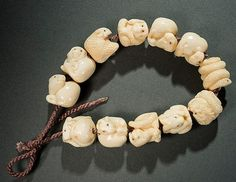 "YASUFUSA: STRING OF THE ZODIAC ANIMALS  Ivory. Japan, 20th cent. This very rare and complete string of twelve ojime pearls is extraordinary. Each ojime depicts a three-dimensional animal of the zodiac circle appearing in perfect order. Each individual depiction is expertly rounded, the tiny eyes are inlaid and every single ojime signed YASU-FUSA within a reserve. The artist, born in 1931, is included in the book ""Living Masters of Netsuke"" by M. Kinsey. HEIGHT EACH 17-18 MM,"