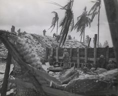 """Marines Swarm an Enbankment, Tarawa, November 1943  """"It was Tough But They Were Tougher-Marines swarm up an embankment on Tarawa in search of Japanese who either fell back or fought from reinforced pill boxes. Taking the island was described as a tough fight but the Leathernecks were tougher."""""""
