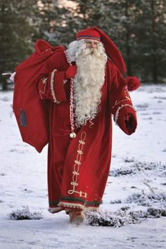 Santa Claus dressed in a traditional Finnish costume, totes a bag of toys in Rovaniemi, Finland