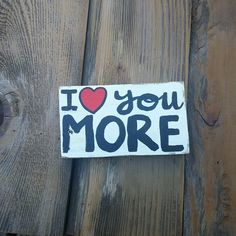 I Love You More Decorative Wood Block, I Love You More, I Love You More Wood Pallet Sign, Wood Sign, Hand Painted Wood Sign. I Love You More! This decorative block is hand painted on reclaimed wood in red, black, and white. It measures approximately 4x5 inches and looks cute on a shelf, nightstand, or desk! Item is made to order and may vary slightly from the picture, all wood and hand paint jobs are not identical; this ensures that you have an original piece all your own. Item is weather...
