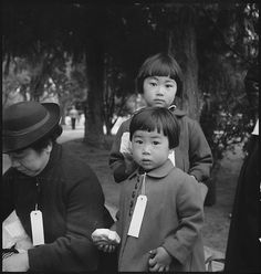 Two children of the Mochida family awaiting evacuation bus to internment camp, 1942. Dorothea Lange.