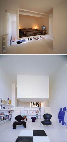 O dono de um pequeno loft de apenas 50m² desafiou os arquitetos que planejavam o espaço a criar um quarto que não sacrificasse os já reduzidos espaços de convivência comum, como a pequena sala de estar e a salinha de jantar. Depois de muito pensar, os arquitetos chegaram a conclusão de o que o melhor a se fazer seria um… quarto suspenso. Abaixo vista do quarto suspenso e da sala de estar. O quarto do casal é um grande cubo de concreto preso no teto.