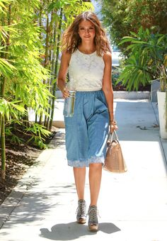 Jessica's got a lot going on. There's the double-denim appeal of her lace-up booties and Topshop pocket skirt. Then there's the white embroidered hem, which complements her floral Tart Collections crop top and lends her look a light, feminine touch. And she finishes with the addition of her perforated Chloé Baylee tote and a few bangles.