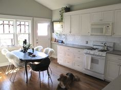 grey wall, white kitchen cabinets