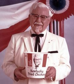 Colonel Harlan Sanders holding a bucket of Kentucky Fried Chicken