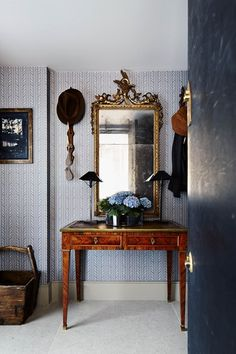 an antique gilded mirror and mahogany console set the mood of the interiors.