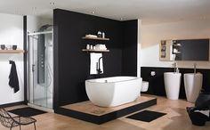 salle de bain design avec baignoire îlot qui trône au milieu de la pièce, vasque sur pied et douche à l'italienne