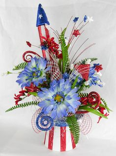 It's all here in this fun patriotic arrangement filled to overflowing with red, white and blue sparkle elements in an Unc. The rocket is surrounded with fern, red fressias and star picks wi Fourth Of July Decor, 4th Of July Decorations, 4th Of July Party, July 4th, 4th Of July Wreath, Stage Decorations, Wedding Decorations, Christmas Decorations, Wedding Ideas