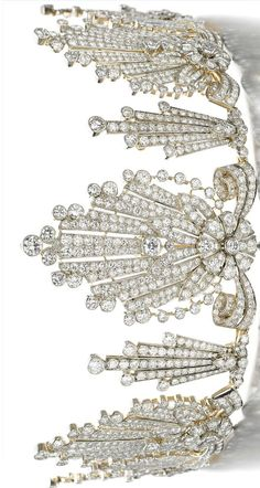 DIAMOND TIARA, 1950s, designed as a graduated series of radiating fans, each centering on a flower head and foliate motif respectively, set with circular-, single- and rose-cut diamonds, inner circumference approximately 310mm, detachable, w/fitted tiara case.