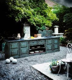 Buffet and painted furniture. I love it in that outdoor setting, but I'm going to need mine in the house. :) Not that it really rains in Texas these days.