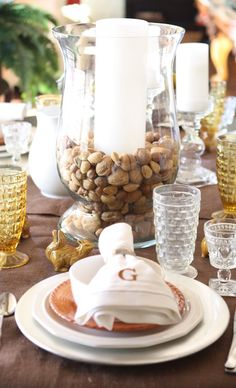 Large glass hurricane from #Goodwill  filled with mixed nuts with a candle placed in the center for a #Thanksgiving centerpiece.  #thrift