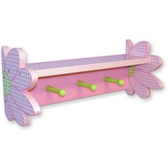 """Give your daughter's room that girlie touch with this Darling Daisy Pink and White Floral Shelf with Pegs! The light purple and pink combination gives this wall shelf a gentle, feminine touch, and the flower-shaped edges completes the shelf. The pegs are a wonderful addition - your daughter can use it to hang her clothing she'll be wearing for the next day. Convenient! Some assembly required. 18"""" long x 8"""" high x 7"""" wide #timelesstreasure"""