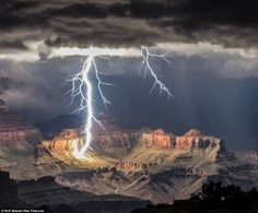 Photographer Rolf Maeder captures incredible moment ferocious lightning bolt hits the Grand Canyon.The area experiences localised thundertsorms in the summer as high temperatures combine with moisture.Huge streaks of white light illuminated the surrounding skies as the thunderstorm's gloomy, grey clouds gathered in Nevada in front of the setting sun.