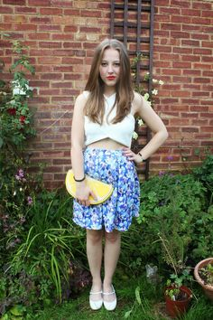 Shop this look for $80:  http://lookastic.com/women/looks/white-cropped-top-and-blue-skater-skirt-and-yellow-clutch-and-white-ballerina-shoes/3106  — White Cropped Top  — Blue Floral Skater Skirt  — Yellow Print Clutch  — White Leather Ballerina Shoes