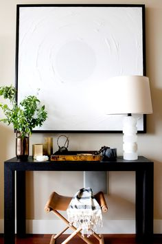 White table lamp and artwork above styled console table