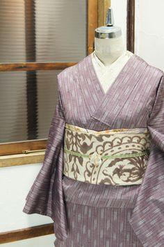 グレーに近いスモーキーなローズラベンダー色に白の絣模様が繊細なアクセントになったストライプが織り出された正絹紬の単着物です。