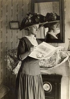 A photograph of a lady reading a newspaper (or magazine?). It dates from 1910, and was originally a photo-postcard sent to an address in New...