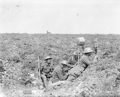WWI-Members of the British Royal Garrison Artillery using a daylight signalling lamp in a shell hole in front of Fricourt Wood, September 1916. [John Warwick Brooke] AHC/ qw