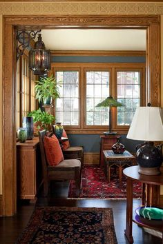 Navy-blue walls work in the bright sunroom; the table lamp by the window is by Century Studios.
