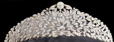 a gorgeous diamond floral tiara, with more elongated leaf fronds than most tiaras, with a bow motif at the base and a large circular diamond a the top