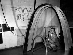 Saarinen rodeado por sus dibujos de arcos históricos, la catenaria suspendida y los modelos de arcos para el proyecto de San Luis