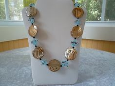 Taupe and black swirl beads with aqua and black beads.