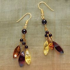 Three multi-colored petals of genuine Baltic amber accented with tiny amber beads hang elegantly from gold plated wires. Earrings hang 2 1/2' from gold plated French wires.
