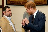 Prince Harry speaks with Andy Reid a former British soldier of the 3rd Batt The Yorkshire Regiment who was badly injured in Afghanistan losing both...