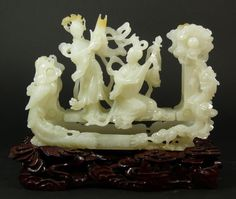"CHINESE WHITE JADE CARVED MAIDENS ON SWINGS An exquisite Chinese hand carved white jade moving sculpture depicting two meirens on swinging platform. One yielding a sheng and the other a pipa. Frame having an intricately carved dragon design with four character calligraphy marks to front center. Magnificent even tone white jade color with russet hints near top. Includes fitted reticulated wood cloud form base. Measures 5"" height x 7 1/2"" width + 1 1/2"" base"
