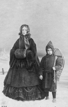 Circa 1860:  A woman and a child carrying snow shoes stand in the snow wearing thick winter clothing. Photo: Otto Herschan, Getty Images / Hulton Archive