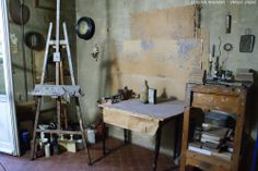 Morandi's painting studio, with his easel and table where he would set out the objects for a still-life composition. On the left you can see is a door with a window, a source of natural light.  Photo © Serena Mignani