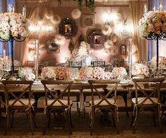 Wooden tables and chairs topped with tall topiaries tapers and low