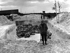 A BBC reporter stands in front of a mass grave at Bergen-Belsen concentration camp, after its liberation by the British army, April 1945. 60,000 civilian prisoners, many suffering from typhus and dysentry were found in the camp. Thousands were already dead. (Photo by Galerie Bilderwelt/Getty Images)
