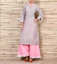 This is a cotton striped kurta with diagnol stripes on the yoke and sleeves eith a pink collar and piping on the frnt with silver buttons. It is paired with pink cotton palazzos with a silver patti on the bottom. Indian Attire, Indian Wear, Indian Outfits, Biba Fashion, Ethnic Fashion, Kurta Designs Women, Blouse Designs, New Dress Pattern, Kurta Patterns