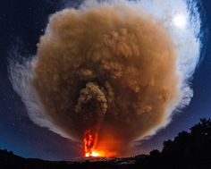 The ash cloud from Mount Etna's Voragine crater lights up the sky.
