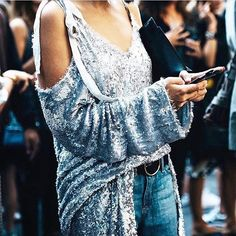 Why not try: tucking your favorite dress into denim to give it a fresh layered look. We love this silver @magdabutrym dress with a cold shoulder. Shop now on #5F. [photo @caroladearmas]