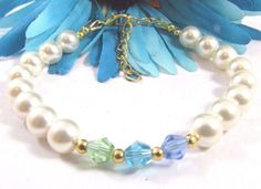 Gorgeous Swarovski Pearl bracelet accented with Swarovski Light Blue Sapphire, Apple Green and Aquamarine crystal beads. Bracelet is Gold Plated with a