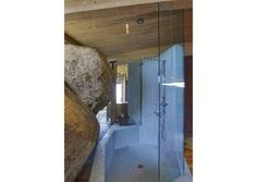 this Malibu home with a rock in the middle provides a very unique place to shower