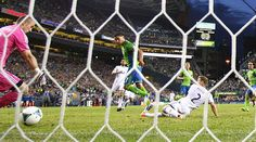 Lamar Neagle, center, sends the ball past Vancouver Whitecaps goalkeeper Brad Knighton to score in the second half, Photo by John Lok / The Seattle Times