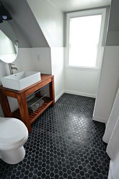 Black mini hexagon tiles have completely transformed the floor of this bathroom.
