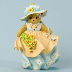 Fig Bear Angel/Flowers  Christina gently cradles the delicate posies she's plucked during her walk alongside the garden. She wears a coordinating bonnet to shade her eyes from the sun. She stands a stately 7-inches tall.