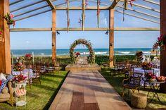 Cerimônia de casamento na praia com arco de flores. Foto: Studio Enzo