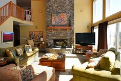 Great room with multi-level stone fireplace, vaulted ceiling with exposed beams and large windows
