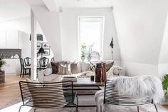 Otwarty salon z kuchnią z białymi ścianami,drewnianą podłogą i czarnymi metalowymi krzesłami i stolikiem